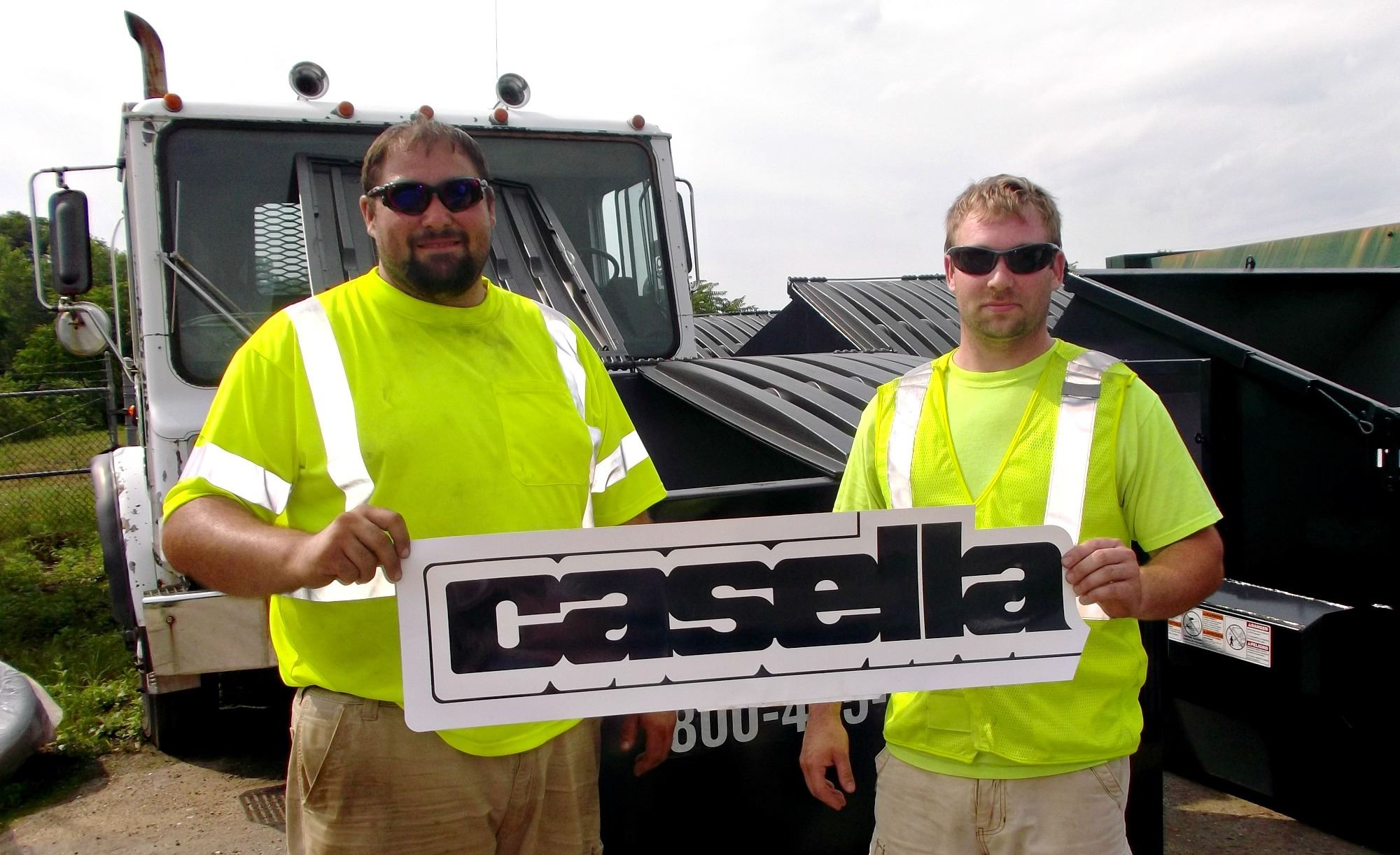 Men Posing with Casella Sign